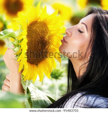 Cute young sensual woman smelling sunflower - stock photo