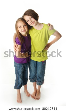 Cute young sisters isolated on white in studio - stock photo
