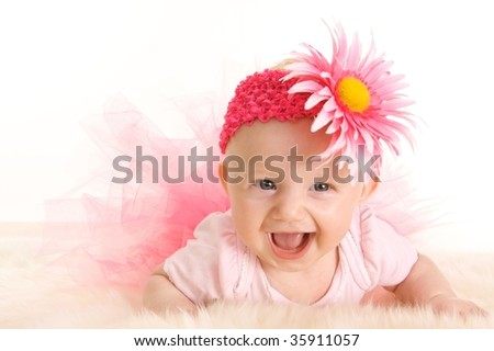 Cute young smiling infant girl in a pink tutu and flower head band - stock photo