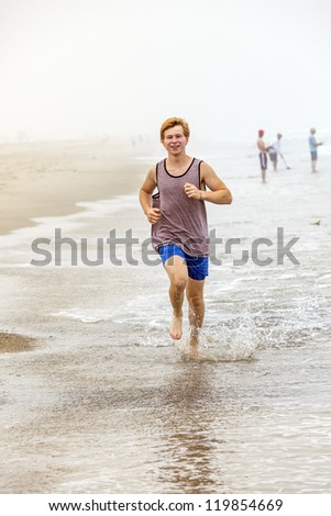 cute young teenage boy jogging at the empty beach in the morning - stock photo