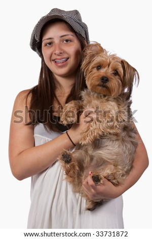 Cute young teenage Hispanic girl with braces wearing a hat holding onto pet Yorkshire Terrier dog