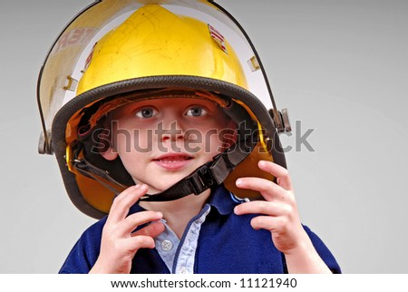 Cute young toddler boy wearing real fireman's helmet - stock photo