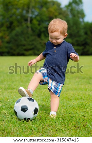 Cute young toddler playing soccer or football - stock photo