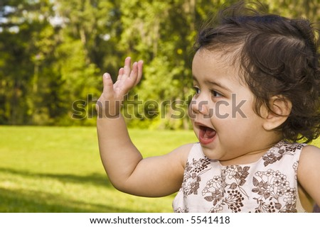 Cute young toddler waves goodbye - stock photo