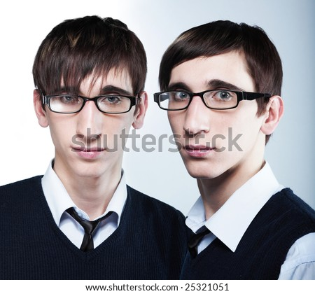 cute young twins with fashion haircuts wearing glasses - stock photo