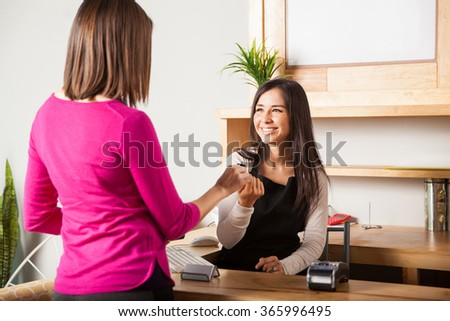 Cute young woman at the cash register taking a credit card from the hand of a customer and smiling - stock photo
