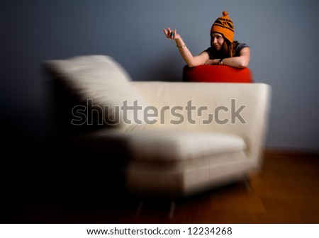 Cute young woman calling you on the sofa. Lounge and relaxation concept. Zoom blur effect