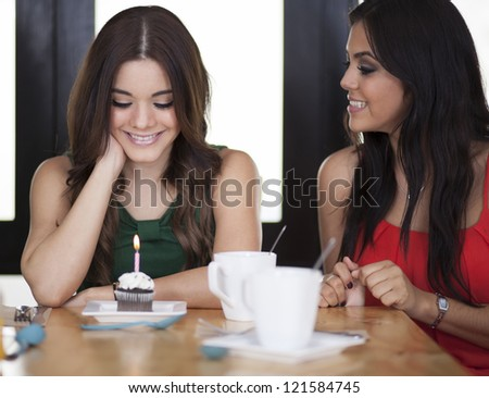 Cute young woman celebrating her birthday with a friend and making a wish
