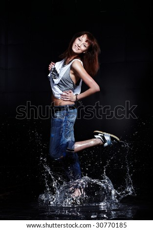 Cute Young woman dancing in water - stock photo