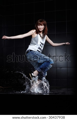 Cute Young woman dancing in water on black - stock photo
