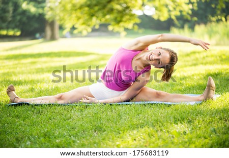 Cute young woman doing stretching exercises in the park. - stock photo