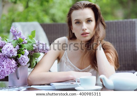 Cute young woman drinking coffee and resting in the garden - stock photo