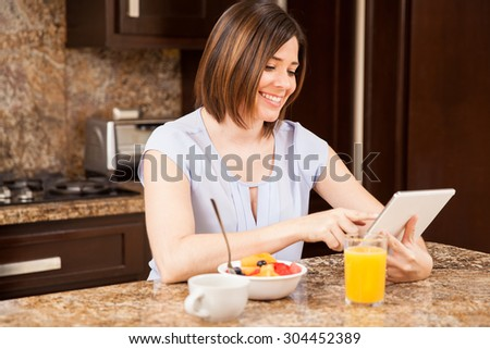 Cute young woman eating a healthy breakfast in the kitchen while social networking in a tablet computer - stock photo