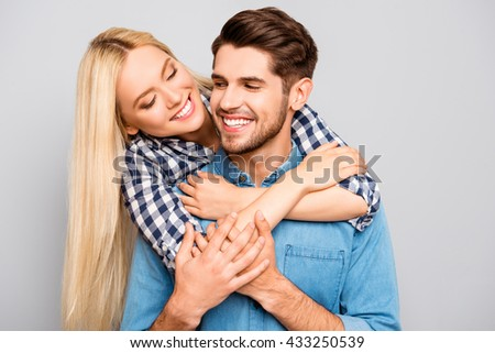 Cute young woman embracing her boyfriend, he carrying her - stock photo