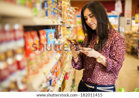 Cute young woman examining a product label while shopping at the store - stock photo