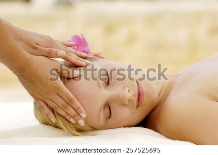 Cute young woman getting a massage on her face - stock photo