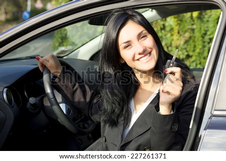Cute young woman happy about new car - stock photo