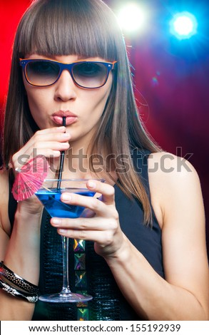 Cute young woman having cocktails at a night club