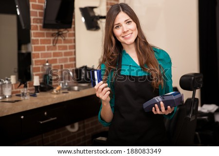 Cute young woman holding a credit card and smiling in a barber shop - stock photo