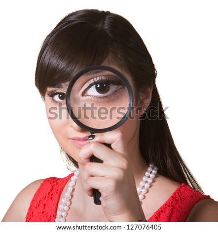 Cute young woman holding a magnifying glass over her eye