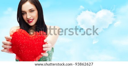 Cute young woman holds a heart symbol against romantic background with lots of copyspace - stock photo