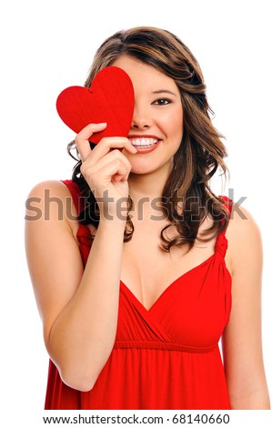 Cute young woman holds a heart symbol to her face - stock photo