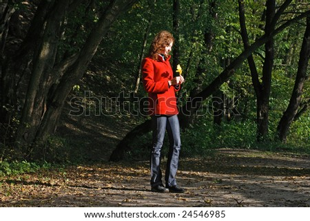 Cute young woman in autumn park - stock photo
