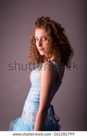 Cute young woman in blue dress in the studio