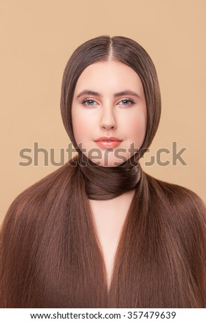 Cute young woman is presenting flexibility of her long hair around neck. She is looking at camera confidently. The lady is standing and smiling. Isolated on brown background - stock photo