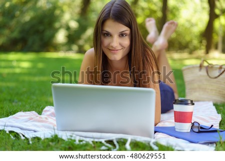 Cute young woman laying down in front of laptop on blanket with cup and eyeglasses outside in park during summer