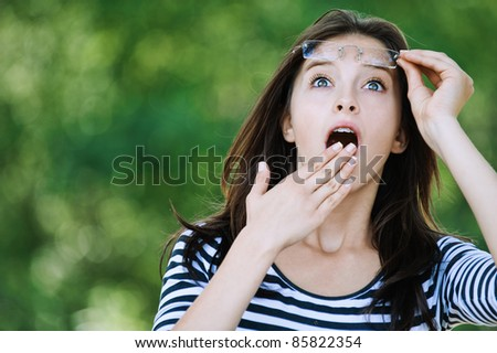 cute young woman looking up surprised raised glasses covers mouth his hand - stock photo