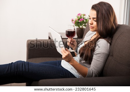 Cute young woman relaxing at home and enjoying a glass of wine while reading - stock photo