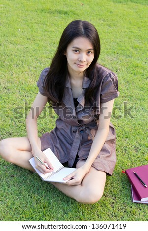 Cute young woman sitting on the grass and writing the book