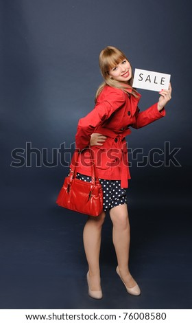 Cute young woman standing with sale sign