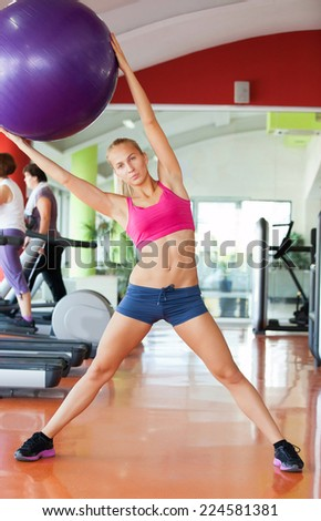 Cute young woman stretching and warming up before working out at a gym