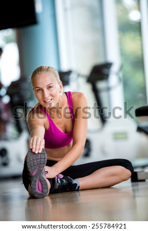 Cute young woman stretching and warming up for her training at a gym - stock photo