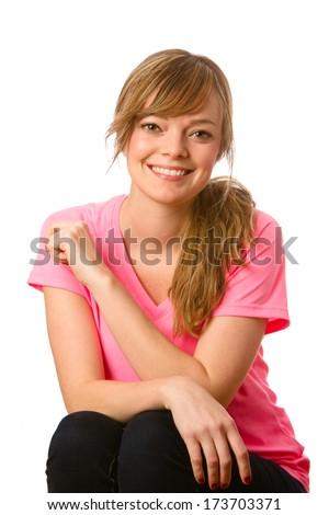 Cute Young Woman - This is a portrait of a beautiful young woman with her hair pulled back wearing a pink V-neck t-shirt. Shot on an isolate white background. - stock photo