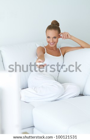Cute young woman watching tv on sofa