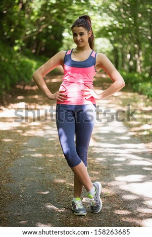 Cute young woman wearing sportswear posing in a forest smiling at camera