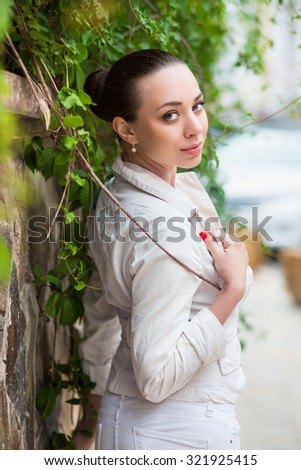 Cute young woman wearing white pants and jacket posing near the wall - stock photo