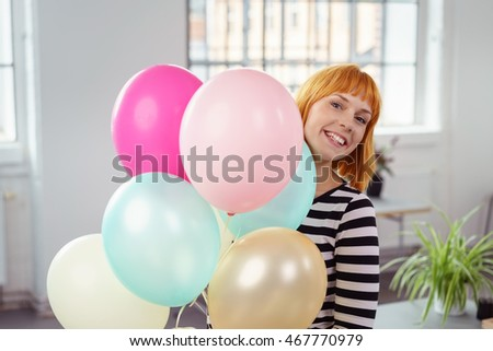 Cute young woman with a bunch of multicolored party balloons in her hands peering around the side with a playful grin in an office