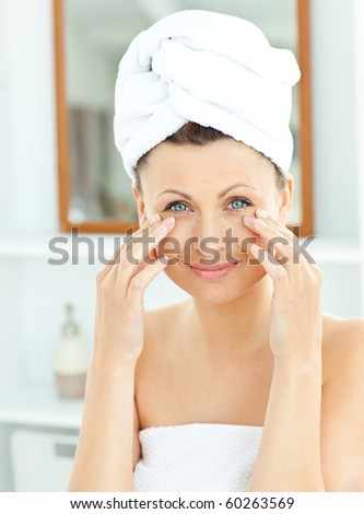 Cute young woman with a towel putting cream on her face in the bathroom at home - stock photo