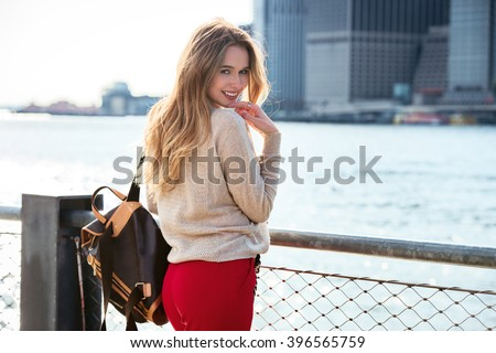 Cute young woman with beautiful smile posing near East River in New York City - stock photo