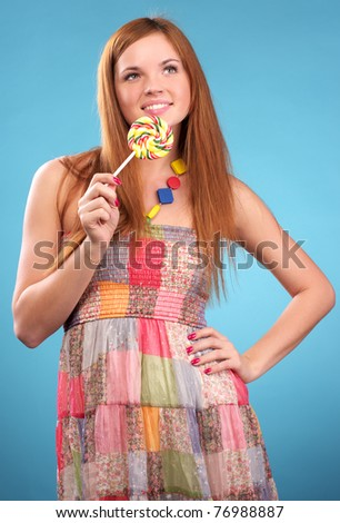 Cute young woman with candy over blue background - stock photo