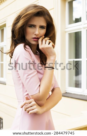 cute young woman with charming expression and natural hair-style posing in fashion outdoor portrait with pink dress and building on background  - stock photo