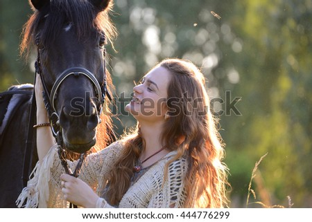 Cute young woman with horse under sunlight of sunset.