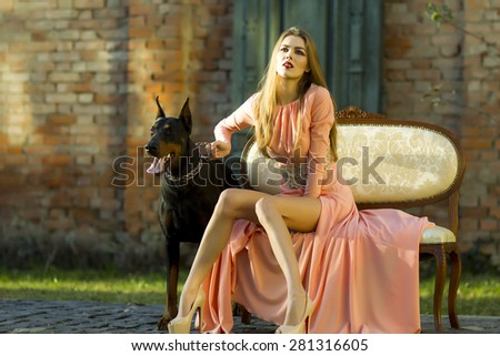 Cute young woman with thoroughbred mastiff sitting on sofa near brick wall building looking away in long peach evening dress outdoor copyspace, horizontal picture - stock photo