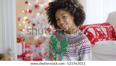 Cute young woman with toy green antlers