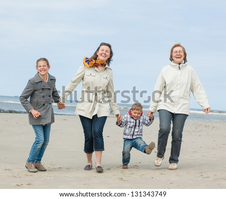 Cute young woman with two kids and grandmother having fun on the Dutch beach