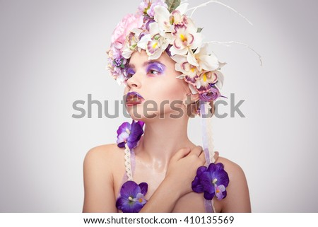 Cute young woman with wreath on head and makeup in purple tones looking away in studio on grey background